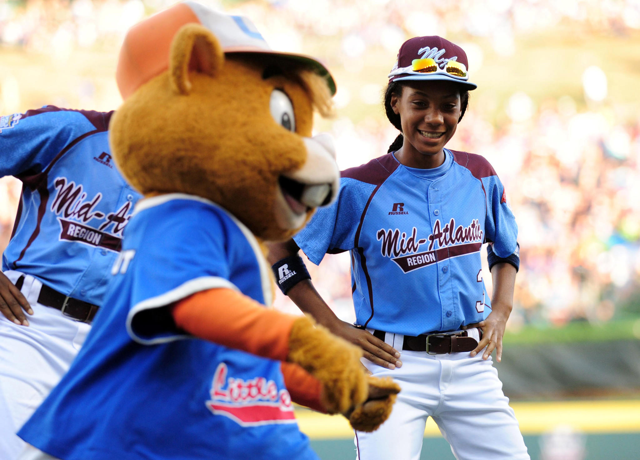 Mid-Atlantic Region third baseman Mo'ne Davis (right) dances with the mascot Dugout prior to the game against the Southwest Region at Lamade Stadium.