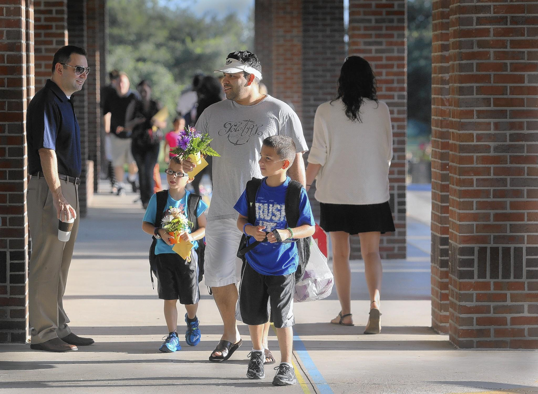 Pablo Medina arrives at Round Lake Elementary School on Monday with sons Gavin, l, 6 and Gabriel, 7, on the first day of school in Lake County. ( Tom Benitez/Orlando Sentinel