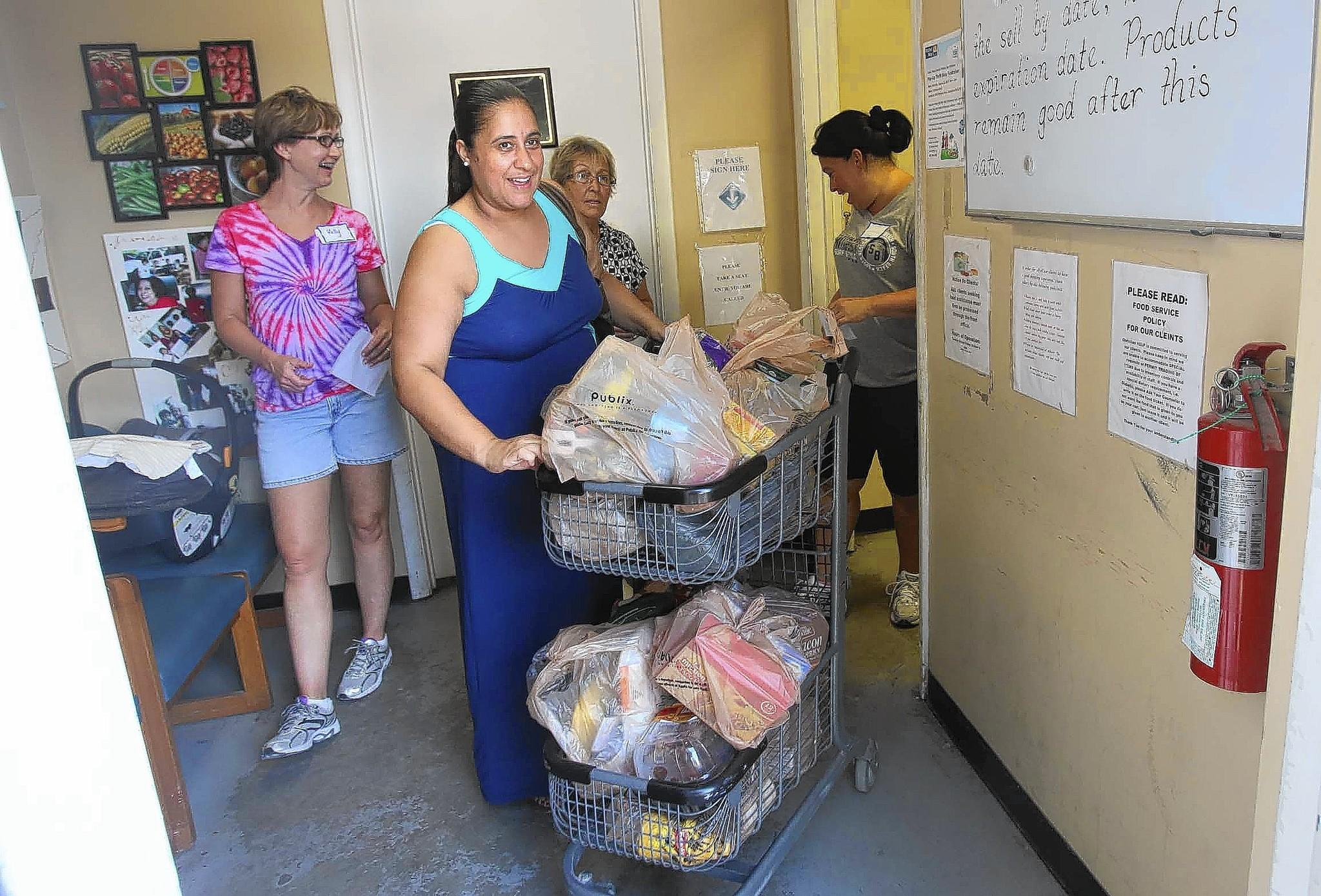 Gleni Peralta takes her basket of groceries from Christian HELP food pantry in Casselberry.