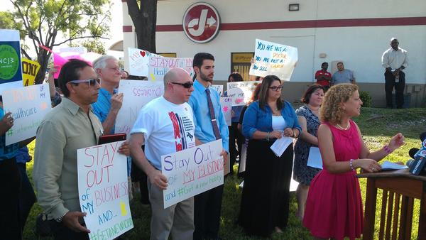 U.S. Rep. Debbie Wasserman Schultz of Weston, chairwoman of the Democratic National Committee, right, speaks out against the Hobby Lobby chain in Davie, Fla., on Aug. 20, 2014. (Photo by Anthony Man)