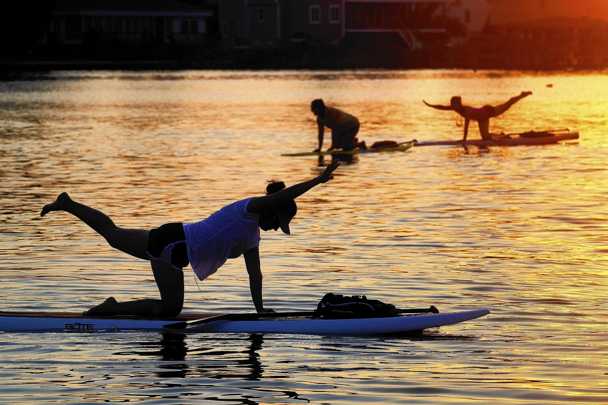 Paddle boarders exercise on their boards while in the water near Whitehouse Cove Marina in Poquoson during a recent Tuesday evening. Every Tuesday evening and Saturday morning, Paddle 757 offers a paddle board fitness class that teaches strength training exercises and basic yoga poses to...