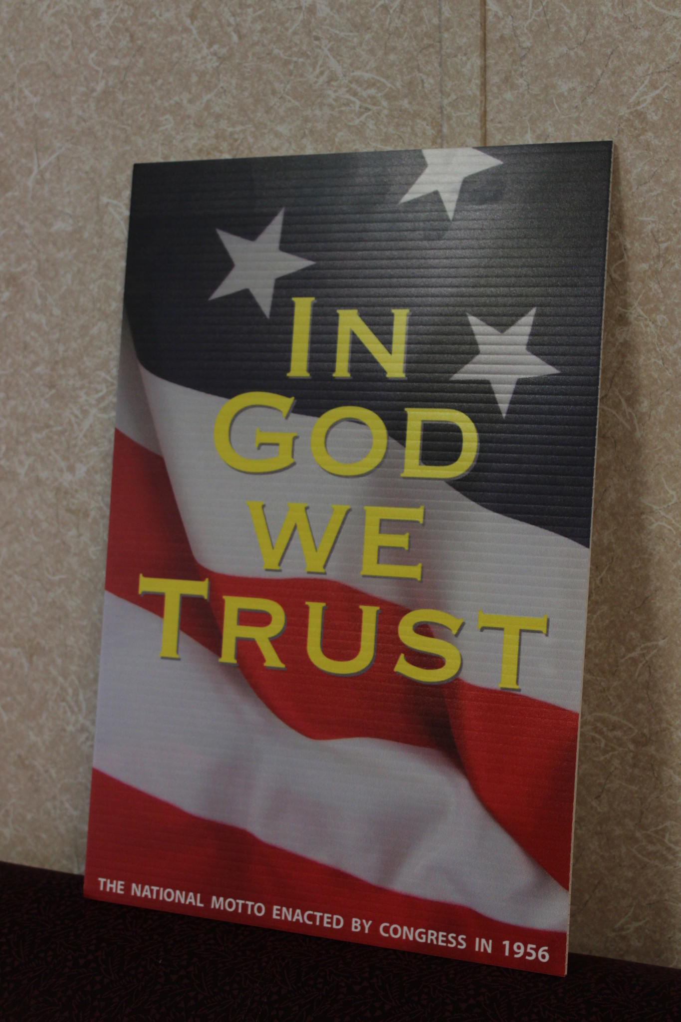 "In the lobby of each Isle of Wight school will be a sign reading ""In God We Trust"" against an American flag background."