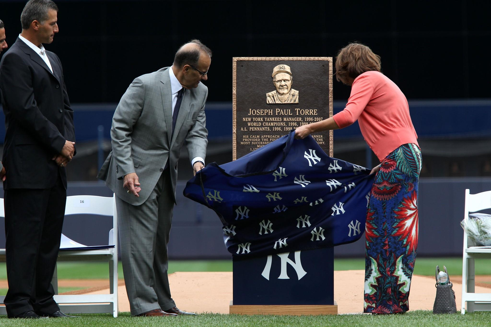 Former Yankees manager Joe Torre and his wife, Ali, unveil a plaque honoring Torre at Yankee Stadium. At left is former Yankees pitcher Andy Pettitte.
