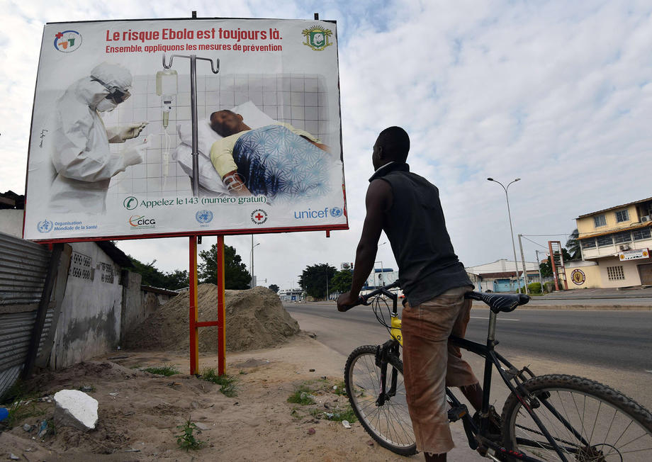 "A man reads a poster raising awareness of the Ebola virus reading ""the risk Ebola is still there. Let us apply the protective measures together\"" on Aug. 24 in Abidjian, Ivory Coast."