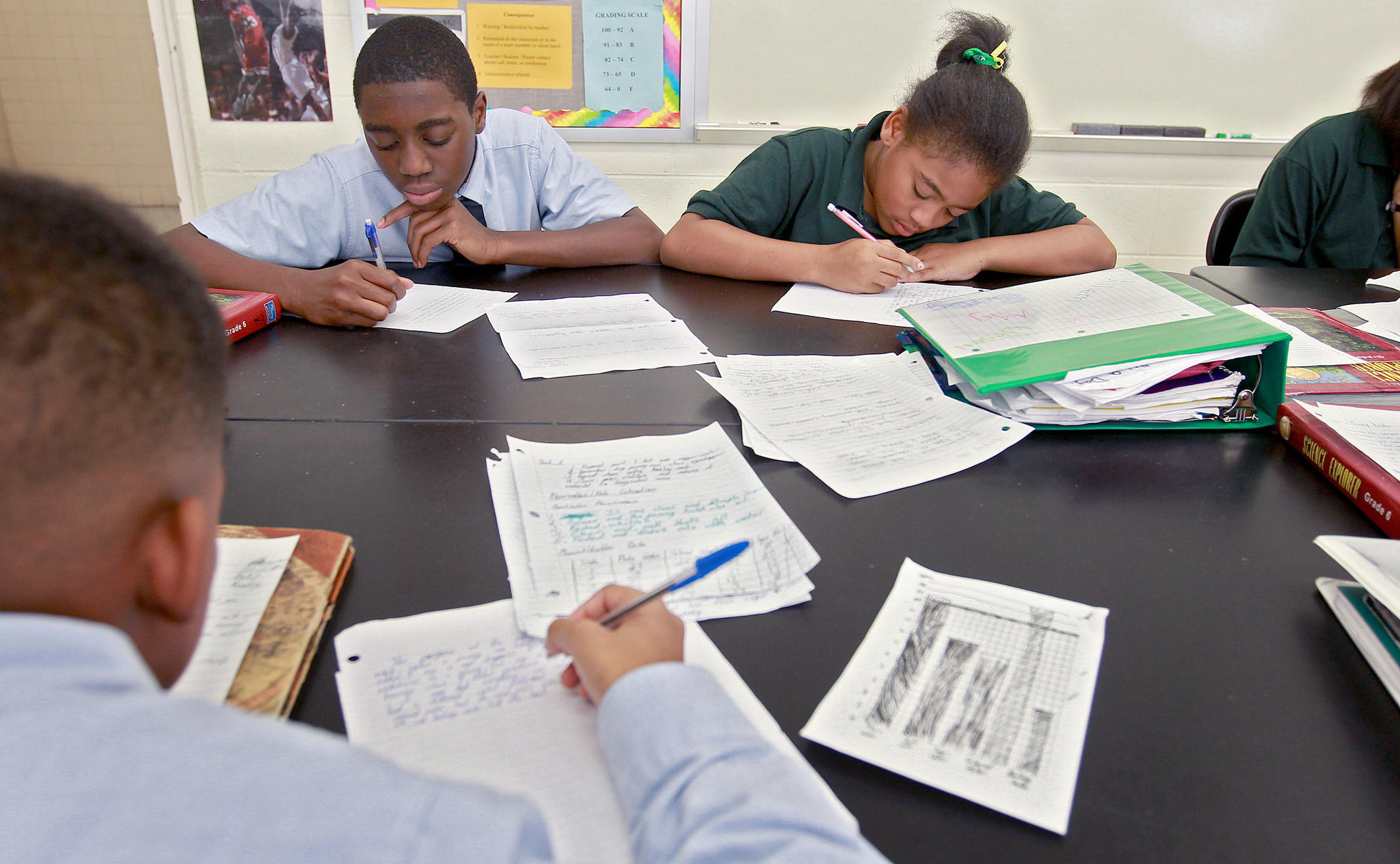 Sixth-grade students Zaiyen Chapman and Ursell Martinez at An Achievable Dream Middle & High School in Newport News work on writing a report on a science experiment that was conducted the previous day.