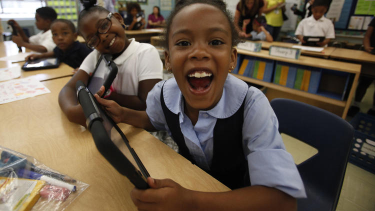 Tiannah Dizadare smiles as she and a school mate explore the possibilities with their new LAUSD provided IPads.