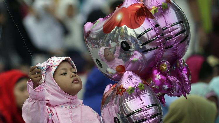 A young girl plays with Hello Kitty balloons