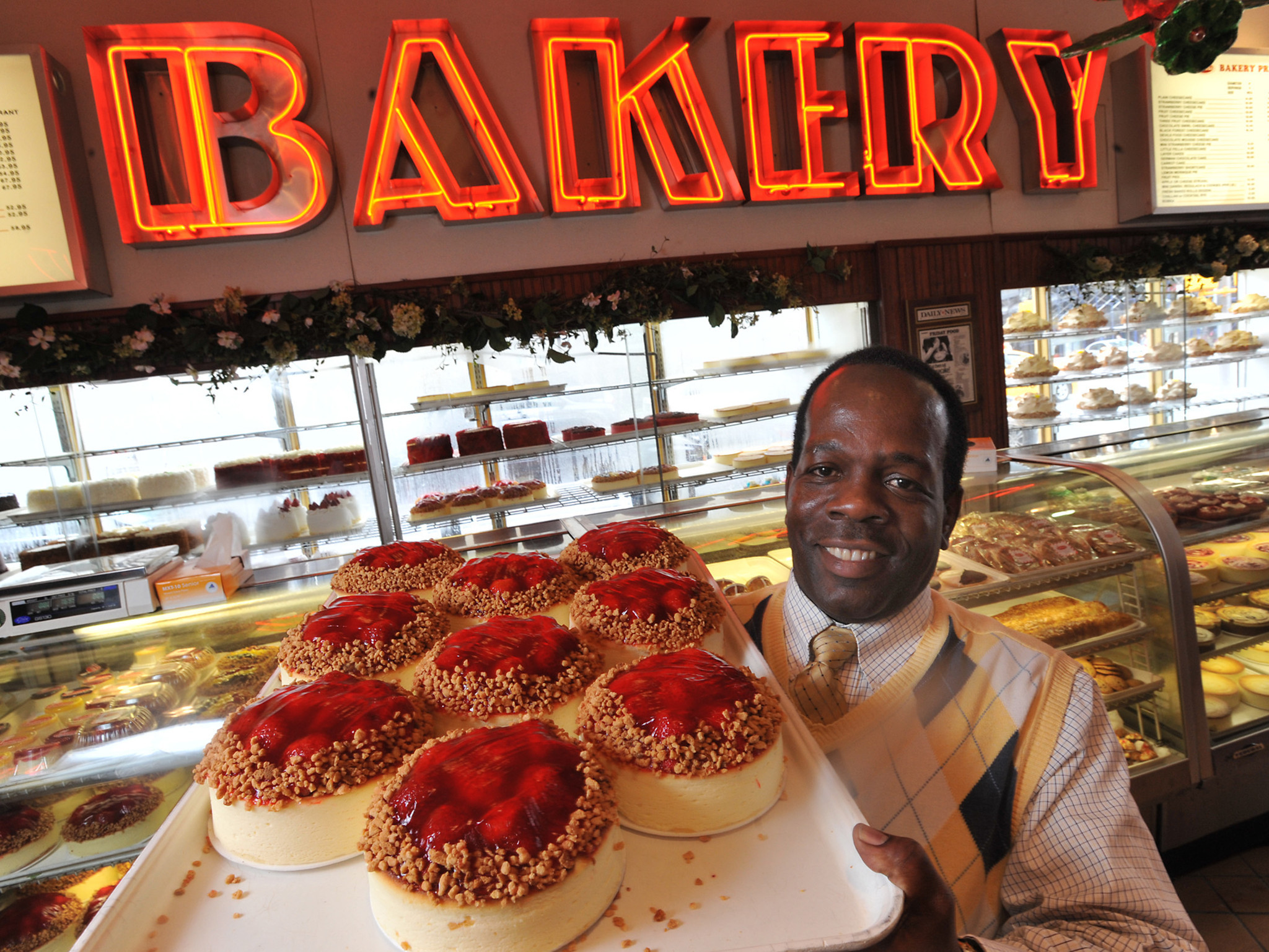 Allen Fleming, general manager of Junior's Cheesecakes in Brooklyn, holds a tray of cheesecakes near the take-out counter inside the institution's original location in downtown Brooklyn on Wednesday, March 21, 2012. /// HARRY FISHER / The Morning Call mc-nyc-Juniors-Cheescakes-032712 March...