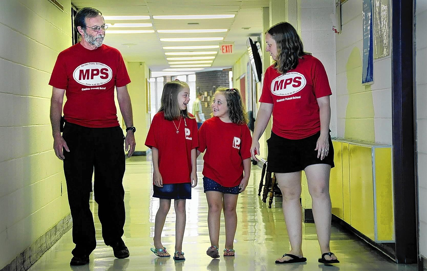 Three generations of Pulaski School teachers and students walk down the hall of the school Tuesday. From left, David Wheeler, 5th grade teacher in his 45th year, his granddaughters, Emily Anastasio, 9, and Katie Anastasio, 6, and his daughter, Jeanne Anastasio, a second grade teacher at the school in her 16th year. Both Wheeler and his daughter are involved in the school's extended learning time program.