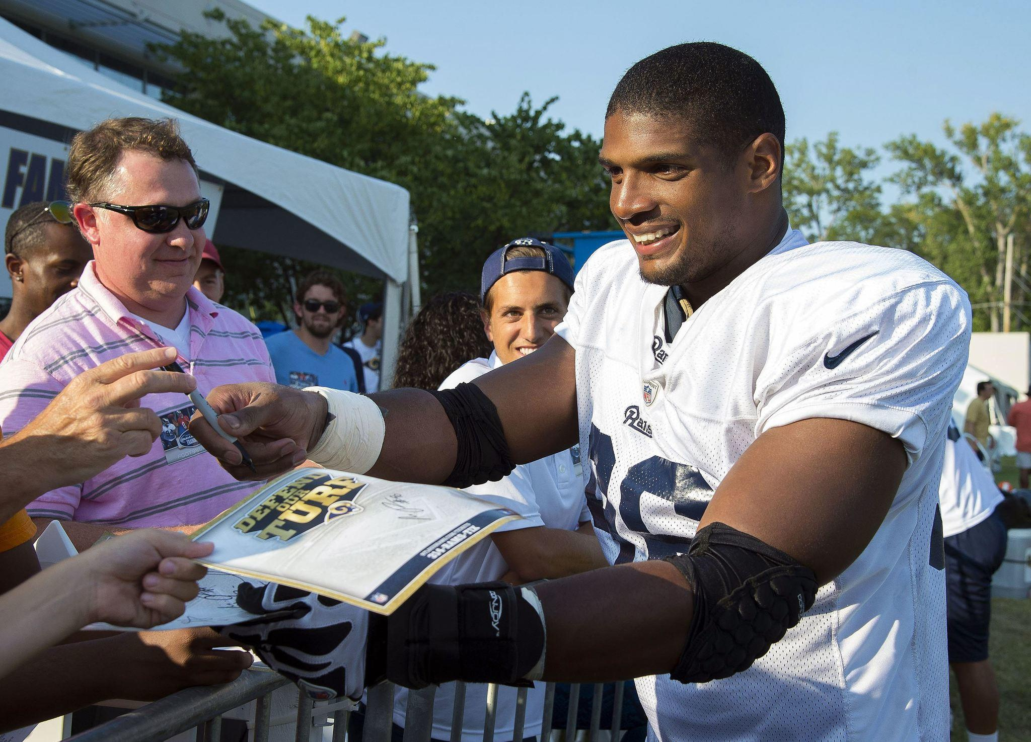 St. Louis Rams defensive lineman Michael Sam signs autographs after practice at Rams Park in this file photo taken in St Louis, Missouri, July 29, 2014. Sports television network ESPN said on Wednesday it regrets a report that detailed the showering habits of St. Louis Rams defensive end Michael Sam, the first openly gay player to be drafted in the NFL.