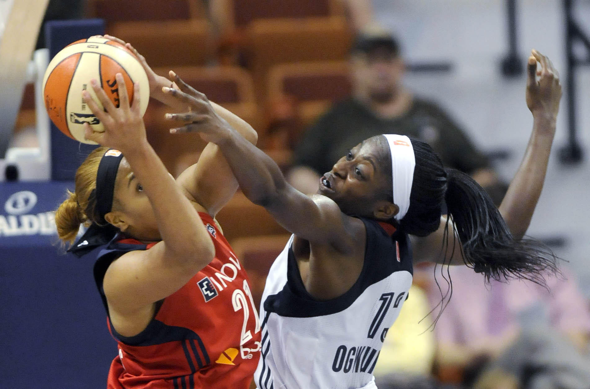 The Connecticut Sun's Chiney Ogwumike (13) fights for a rebound against the Washington Mystics' Tianna Hawkins (21) in the second half at the Mohegan Sun Arena. The Mystics won, 74-66.