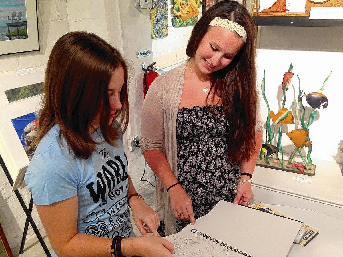 Student Autumn Rose and Gloucester Arts on Main intern Emily Ortiz looking through Rose's sketch book at the meeting. Ortiz helped start the teen mentoring program for GAM through a grant.