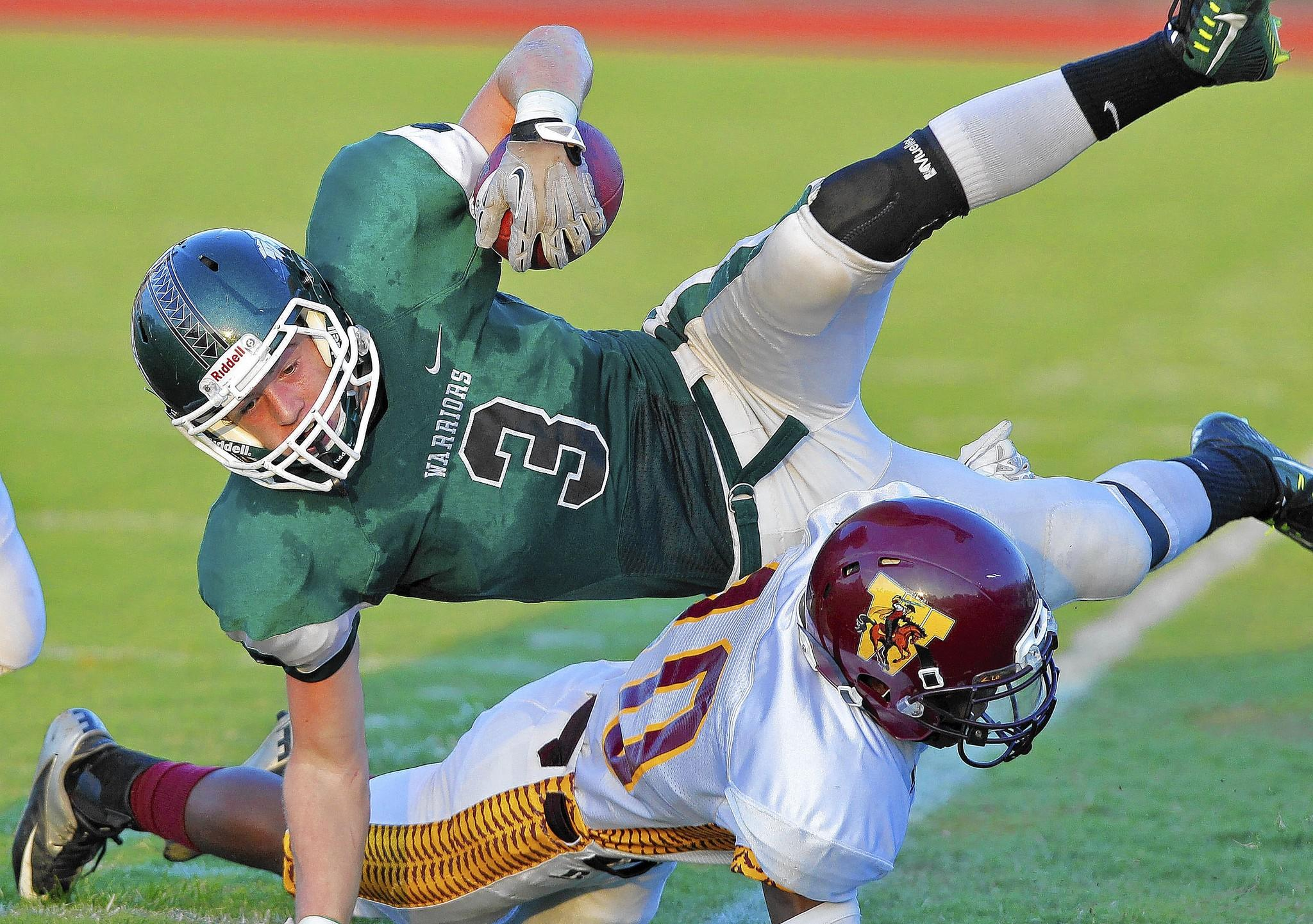 Kecoughtan's Tyler Crist, top, is tackled by Warwick's Travis Williams during Thursday's game at Darling Stadium.