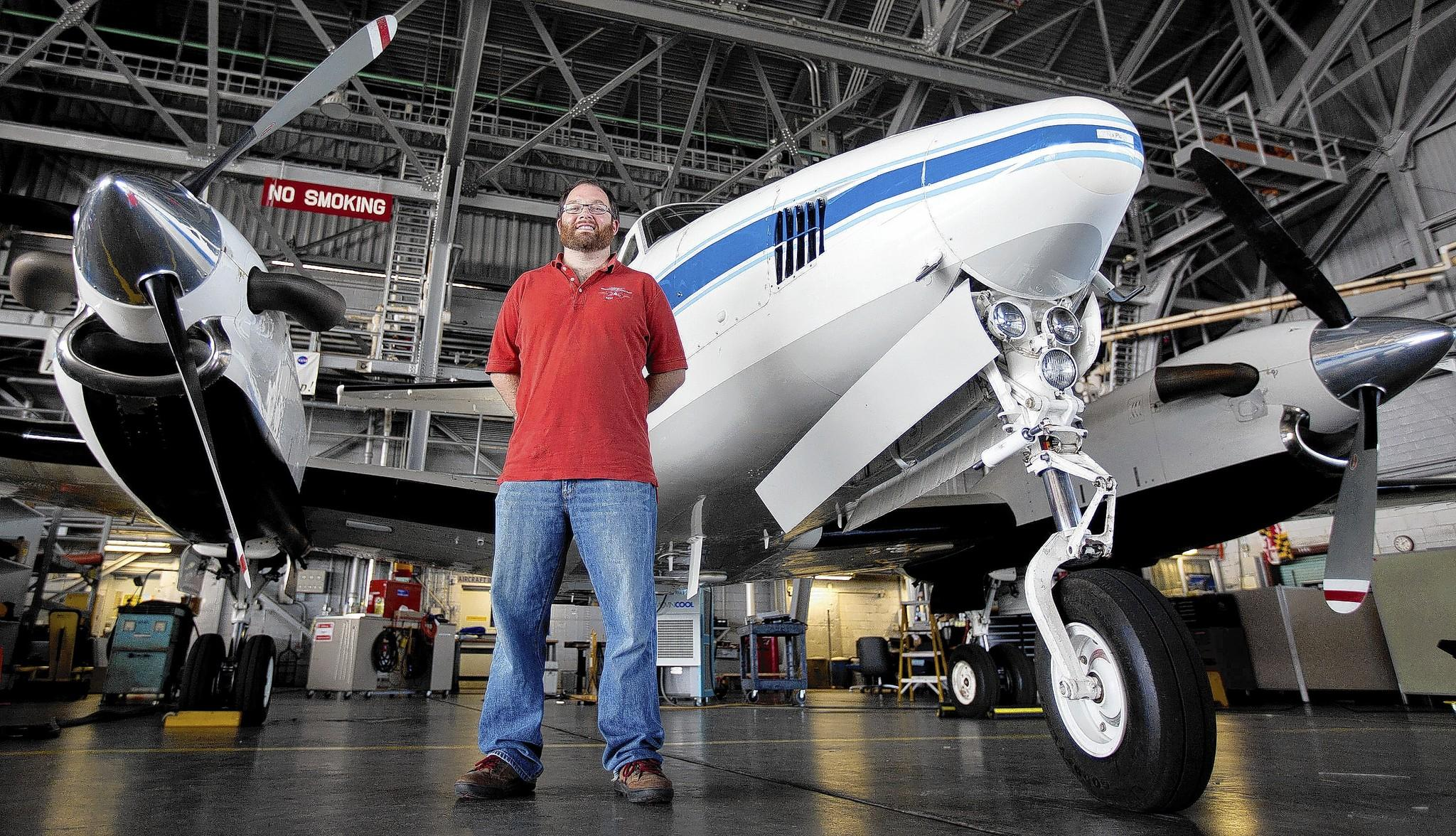 Luke Ziemba, an aerosols scientist at NASA Langley, stands with a King Air B200 aircraft at the NASA Langley hangar on Friday. Ziemba recently returned from a flight aboard a P-3 Hurricane Hunter aircraft with the National Oceanic and Atmospheric Administration to fly through Hurricane Cristobal to study how aerosols can afffect storms.