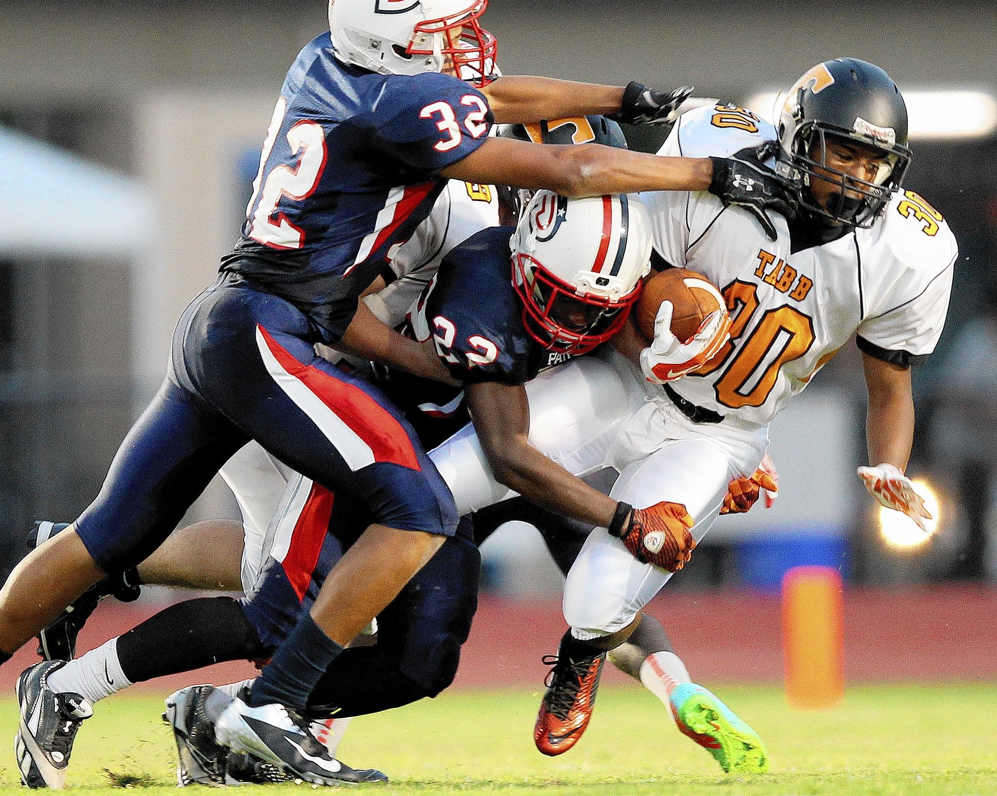 D'Andre McCray of Tabb is dragged down by Javon Brown of Denbigh during the second quarter at Todd Stadium Friday.