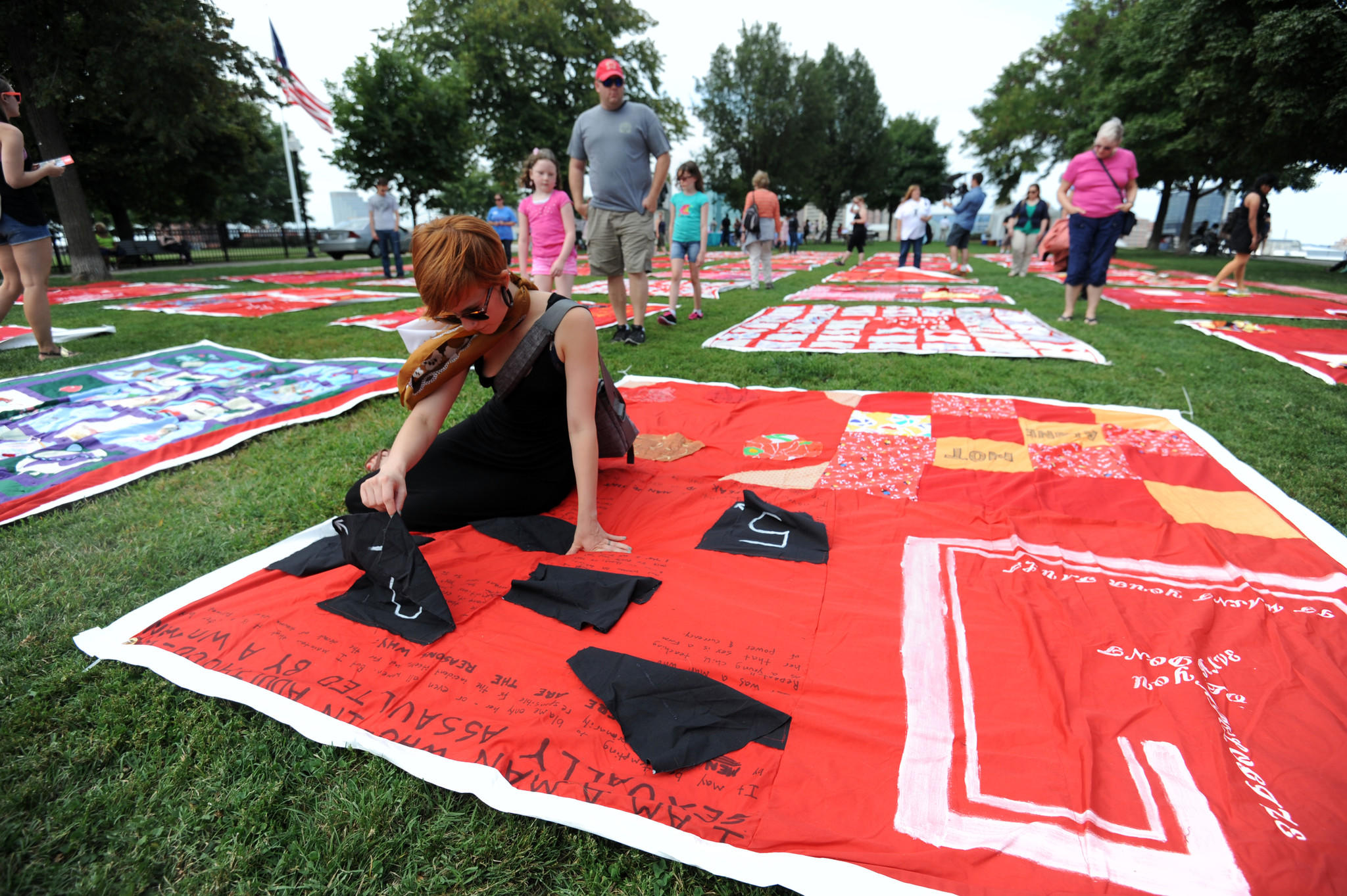 Aliya Webermann, 25, of Baltimore reads one of the stories on a panel of The Monument Quilt. These sections of quilt, dedicated to survivors of rape and abuse, are displayed at Federal Hill Park.