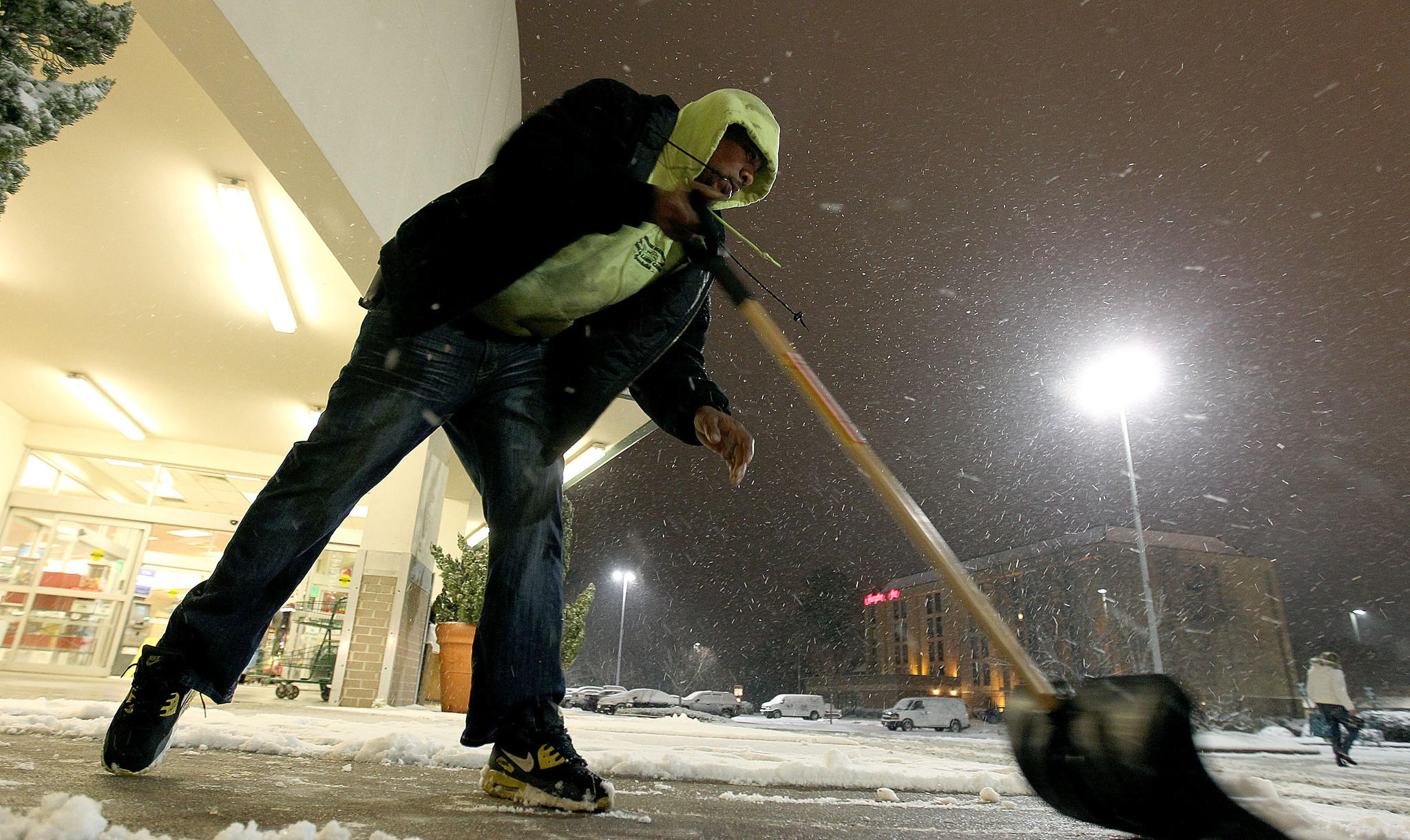 Kwaime Dixon clears the walks in front of the Farm Fresh in the Victory Crossing Shopping Center as the snow begins to taper off Wednesday evening.