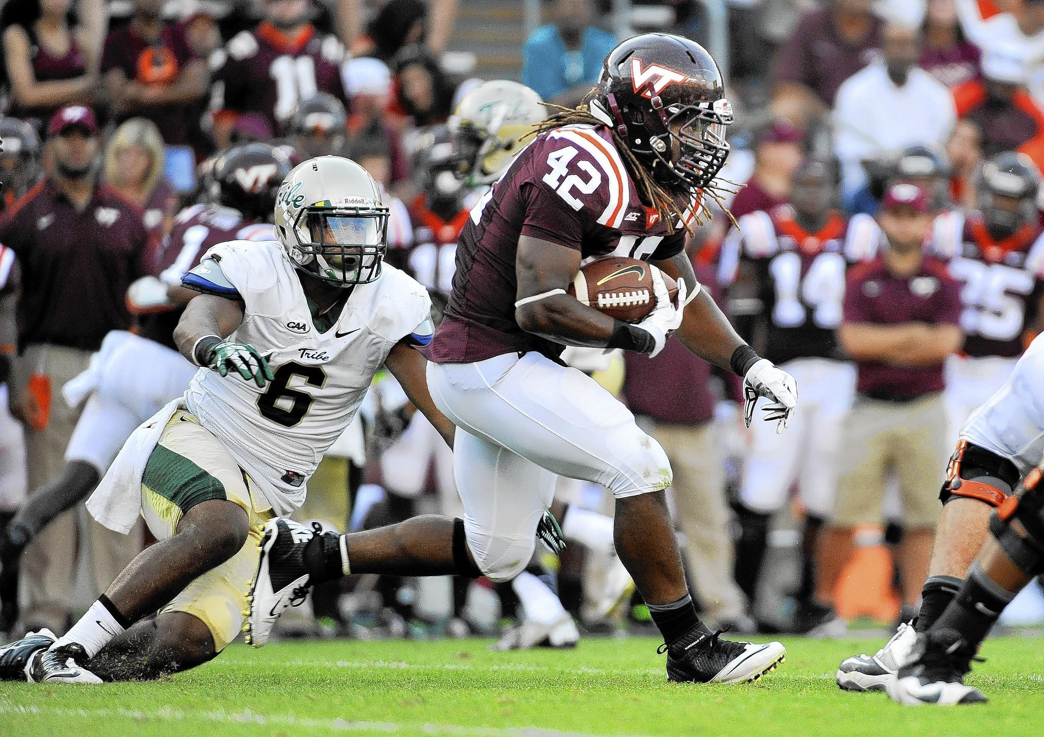 BLACKSBURG, VA - AUGUST 30: Running back Marshawn Williams #42 of the Virginia Tech Hokies rushes against linebacker Airek Green of the William & Mary Tribe at Lane Stadium on August 30, 2014 in Blacksburg, Virginia. Virginia Tech defeated William & Mary 34-9. (Photo by Michael Shroyer/Getty Images) ORG XMIT: 509285383 ** OUTS - ELSENT and FPG - OUTS * NM, PH, VA if sourced by CT, LA or MoD **
