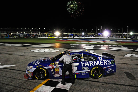 Kasey Kahne, driver of the #5 Farmers Insurance Chevrolet, takes the checkered flag from the official after winning the NASCAR Sprint Cup Series Oral-B USA 500 at Atlanta Motor Speedway on August 31, 2014 in Hampton, Georgia.