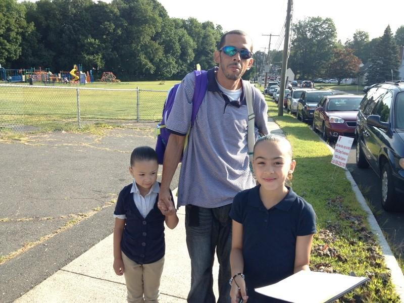Miguel Melendez arrives at Lincoln School in New Britain with his daughters Sharlene, right, and Brianna, left. Sharlene began fifth grade on Tuesday, while Brianna started kindergarten. About 10,000 youngsters across the city started classes for the first day of the new school year.