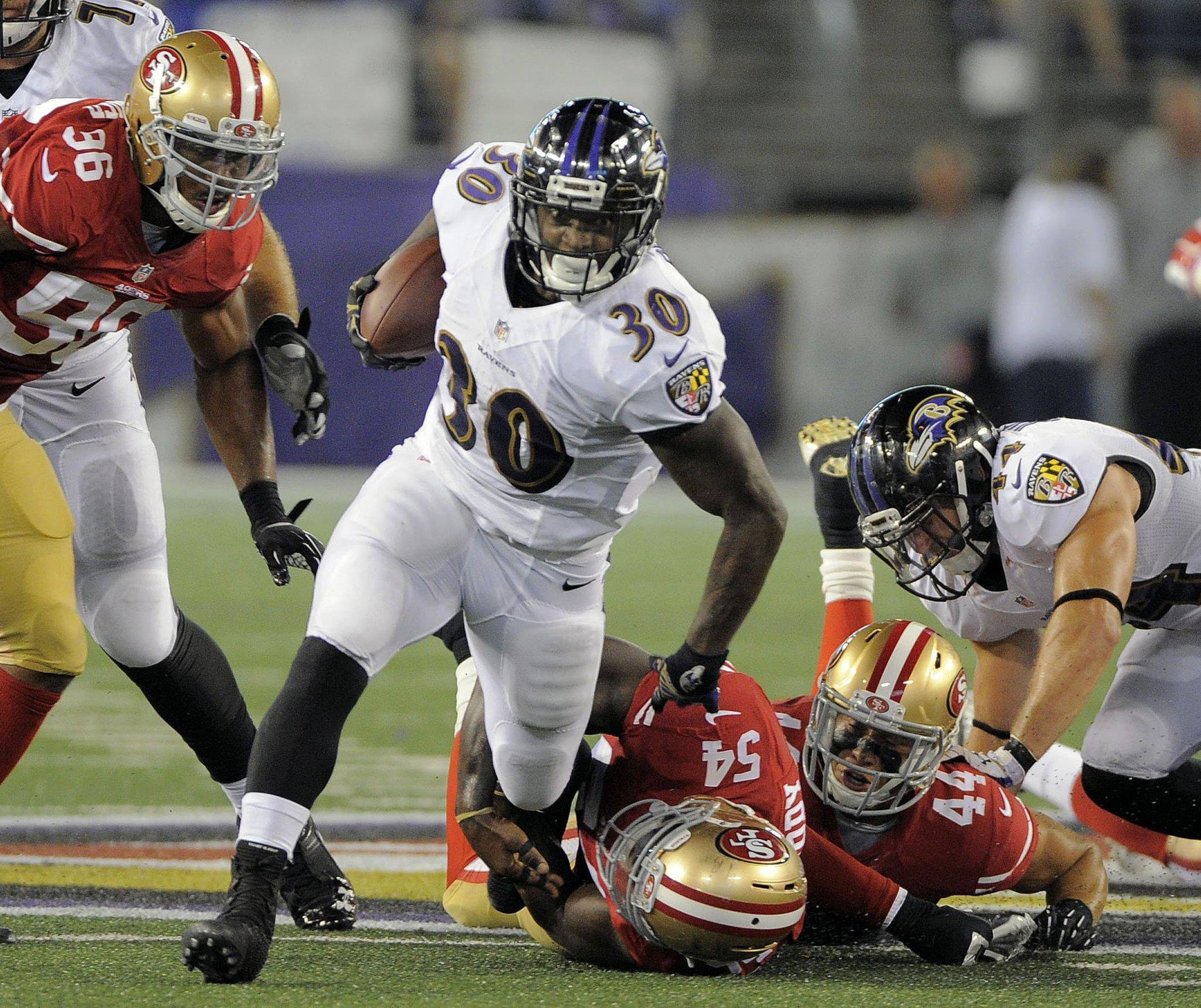 Ravens running back Bernard Pierce breaks through San Francisco 49ers' defense for a first down in the second quarter during preseason action at M & T Bank Stadium.