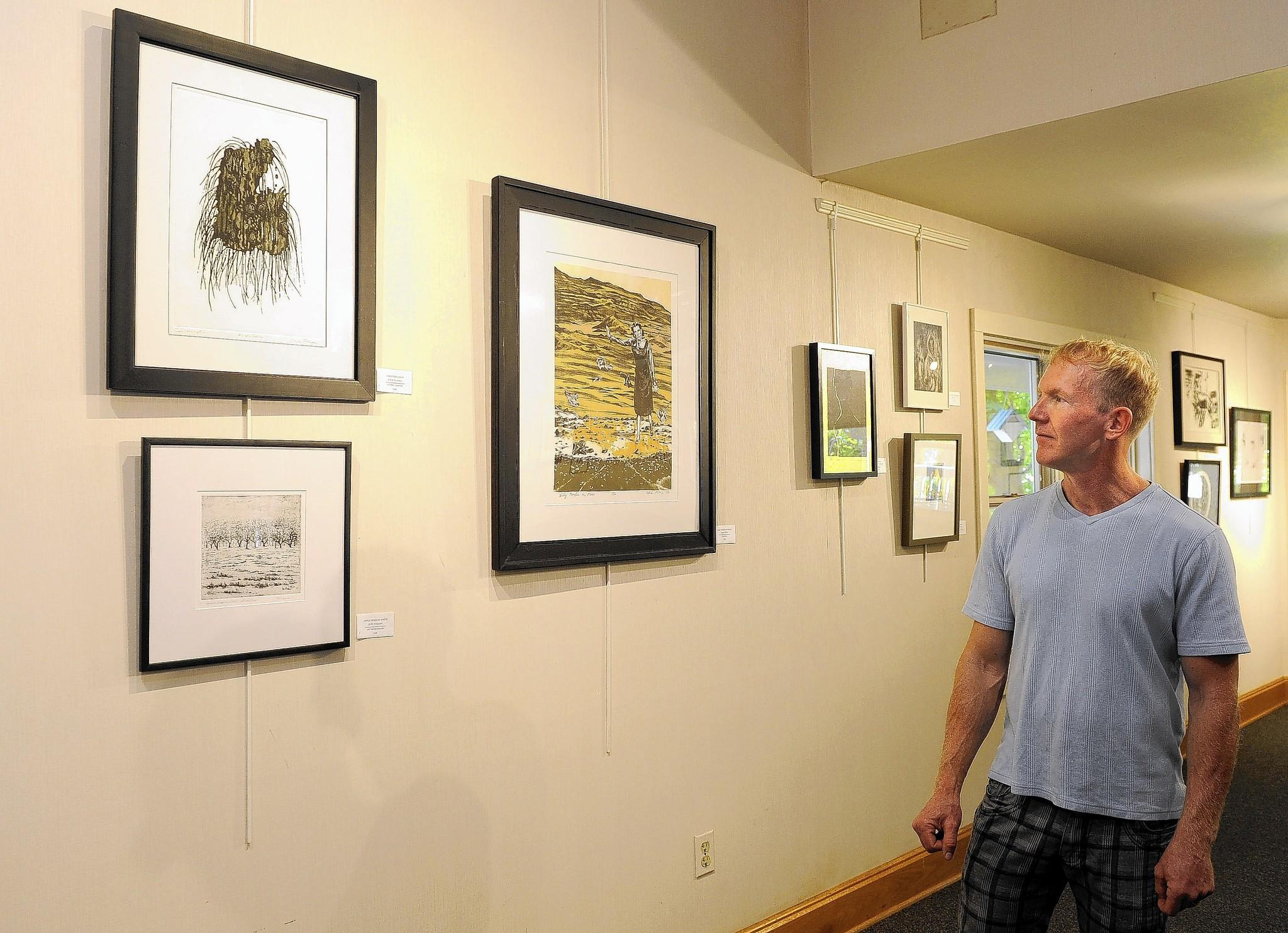 Chris Mona, a professor of art at Anne Arundel community college, looks at works in an exhibit from the printmaking club of the college, which are on display at the gallery at Quiet Waters Park. He is an artist who has work in the show and is also the club's leader.