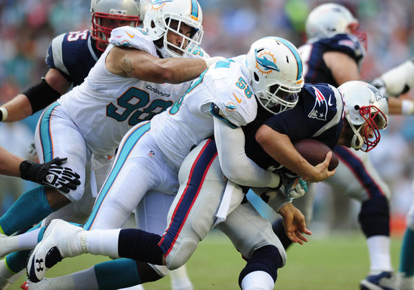Chris McCain of the Dolphins brings down Tom Brady in the fourth quarter.