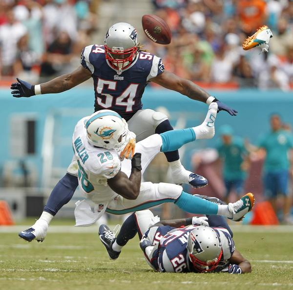 Miami Dolphins running back Lamar Miller (26) fumbles and loses his shoe after getting hit by New England Patriots' Logan Ryan during the second quarter on Sunday, Sept. 7, 2014, at Sun Life Stadium in Miami Gardens, Fla.