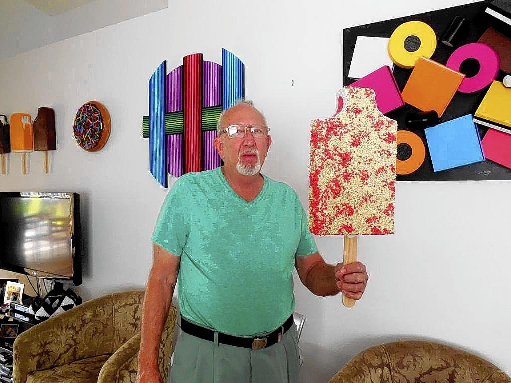 "Local artist Stanford Slutsky holds his work, ""Strawberry Shortcake,"" in front of a wall of his other food art pieces. The work of Slutsky and six other male artists is on display at the Levis JCC in Boca Raton through Oct. 17."