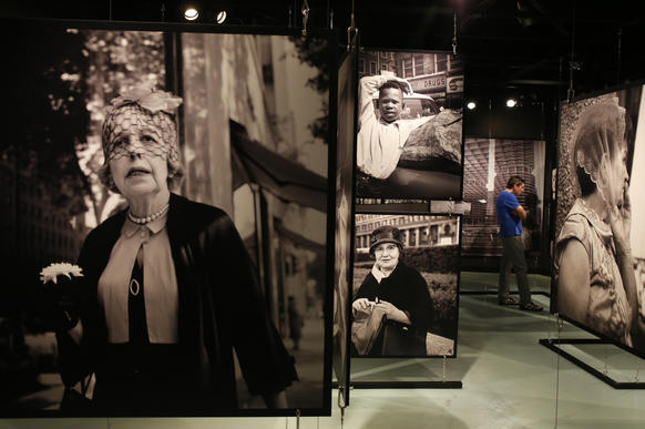 "David Riley, right, from Greensboro, N.C., views photos by street photographer Vivian Maier in the exhibit, ""Vivian Maier's Chicago"" at the Chicago History Museum on the North Side. The rights to her photos are now in dispute."