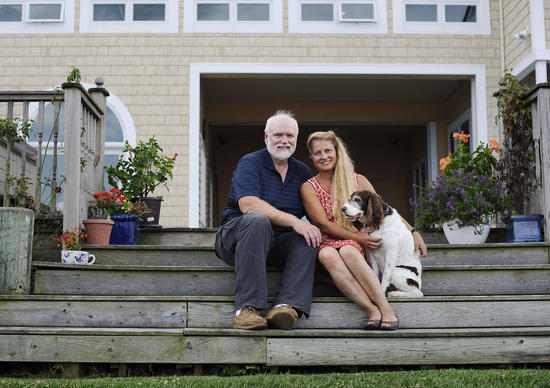 Bill and Jo Ann Loeliger sit with their dog Chai on the steps of their dream home in Essex.