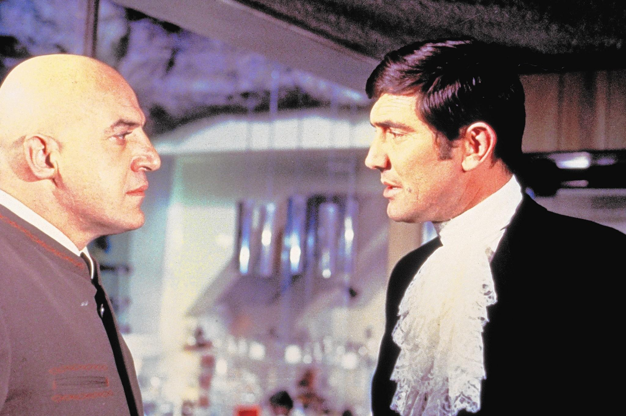 "George Lazenby, right, as James Bond and Telly Savalas as Ernst Stavro Blofeld in ""On Her Majesty's Secret Service."" Lazenby will appear at the Mid-Atlantic Nostalgia Convention."