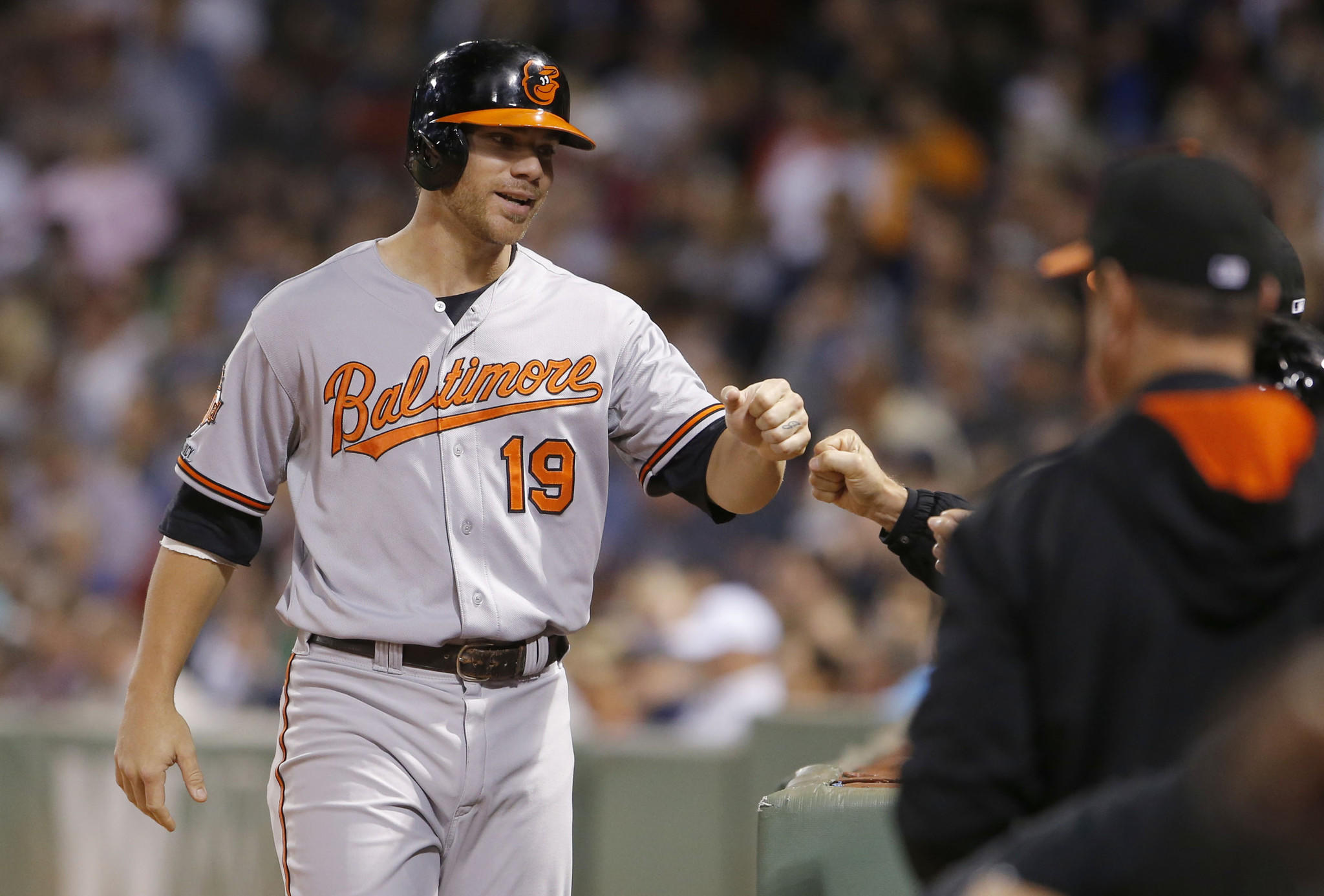 Baltimore Orioles first baseman Chris Davis is congratulated after scoring against the Boston Red Sox.