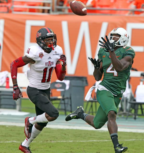 Miami's Phillip Dorsett catches a 64-yard touchdown over Arkansas State's Sterling Young in the first quarter at Sun Life Stadium in Miami Gardens, Fla., on Saturday, Sept. 13, 2014. (Charles Trainor Jr./Miami Herald/MCT)