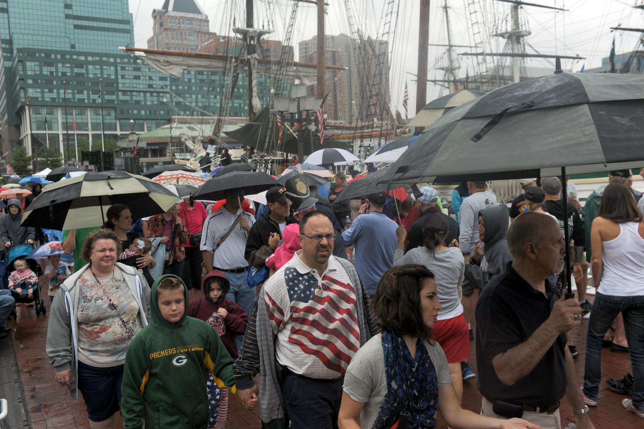 A light rain falls Saturday afternoon during the Star-Spangled Spectacular as people walk along the Inner Harbor promenade.
