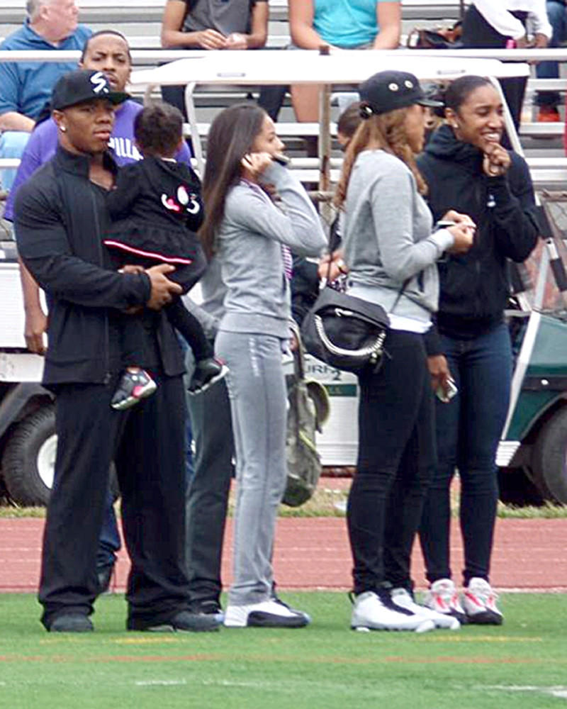 Holding daughter, Ray Rice (left) is photographed on the sidelines of New Rochelle HS football game. Janay is in the black cap.