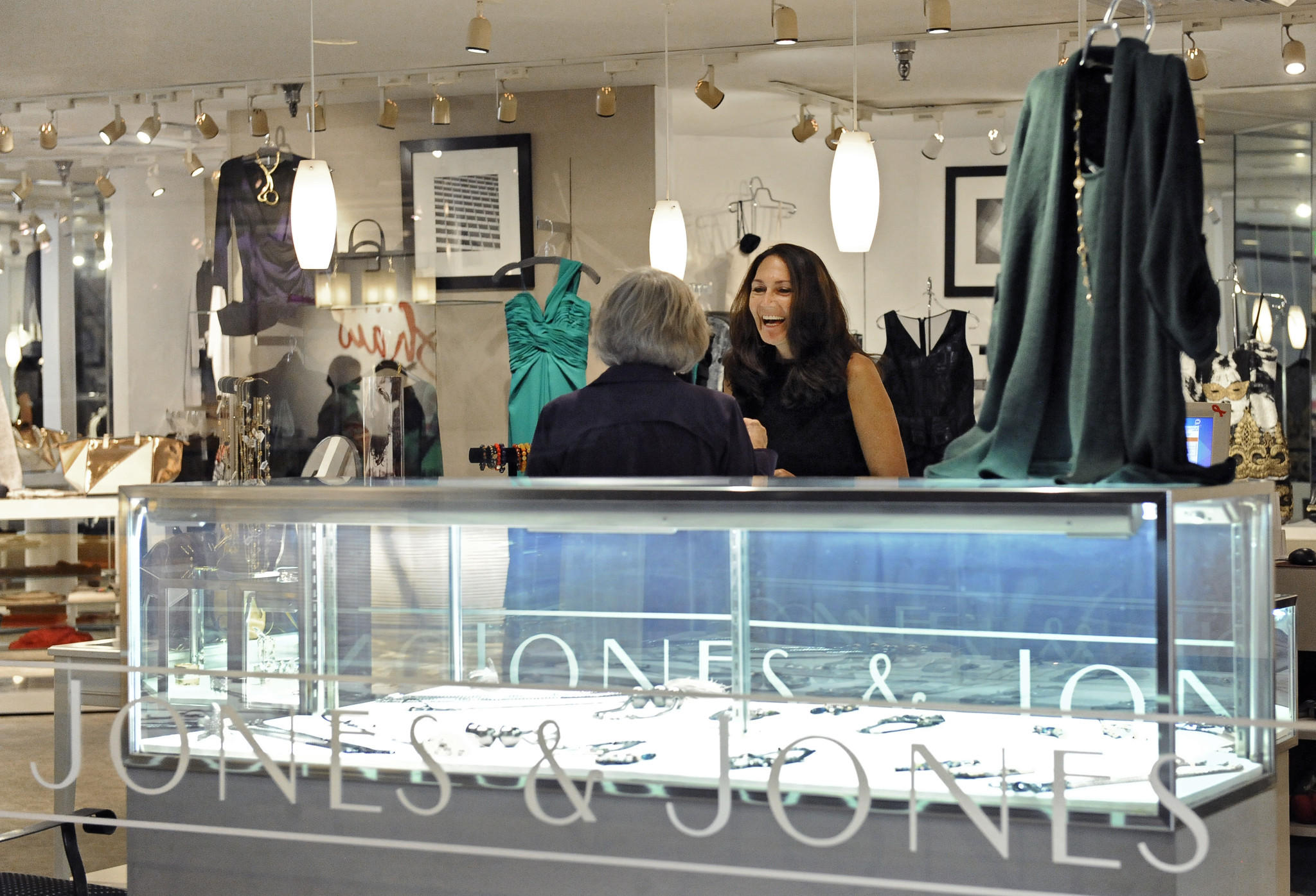 Karen Ciurca-Weiner, right, manager of Jones & Jones boutique at the Village of Cross Keys, helps a customer at the store. The store is participating in an upcoming fashion show to benefit House of Ruth.