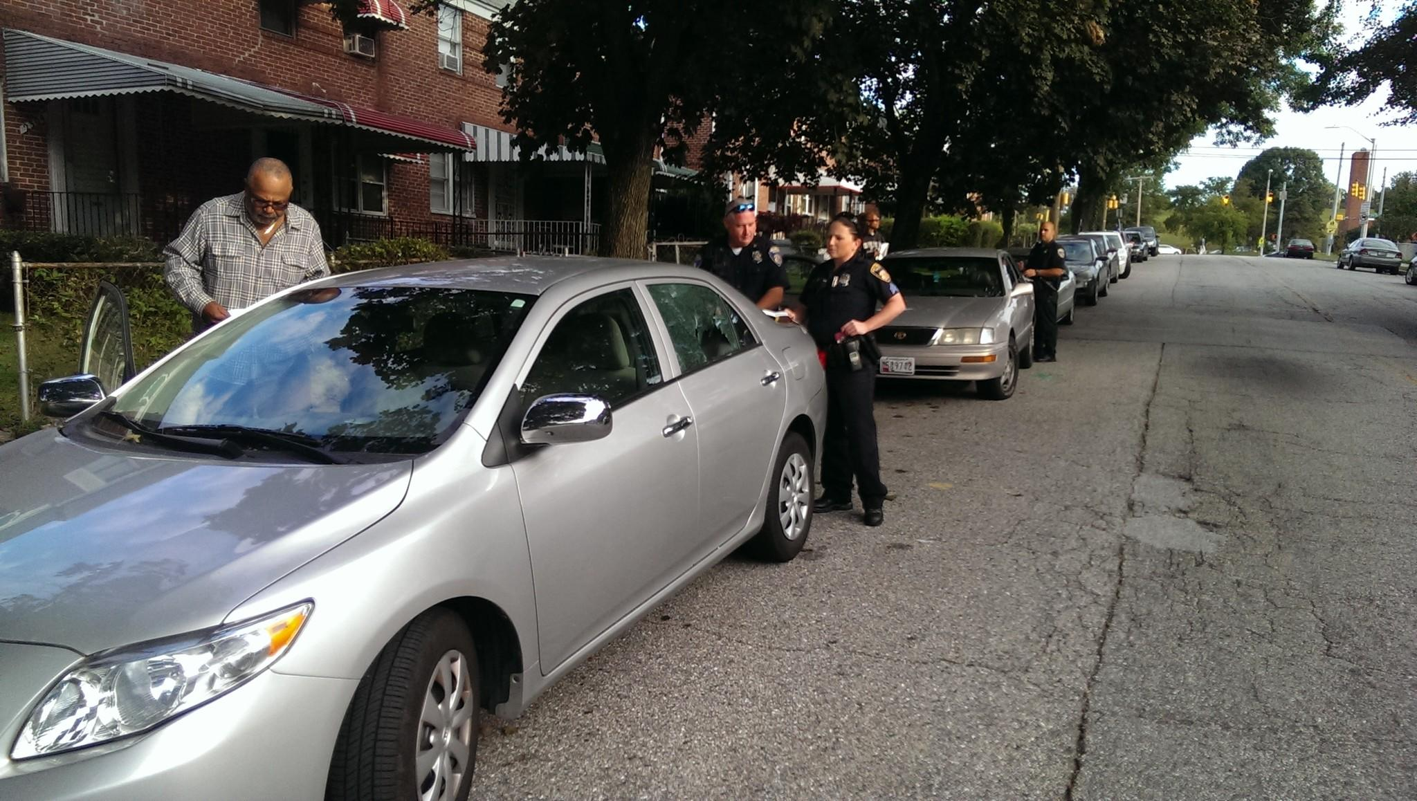 Police officers investigate a car with its window shot out in the 2200 block of N. Dukeland St. Around eight cars in the area were hit.