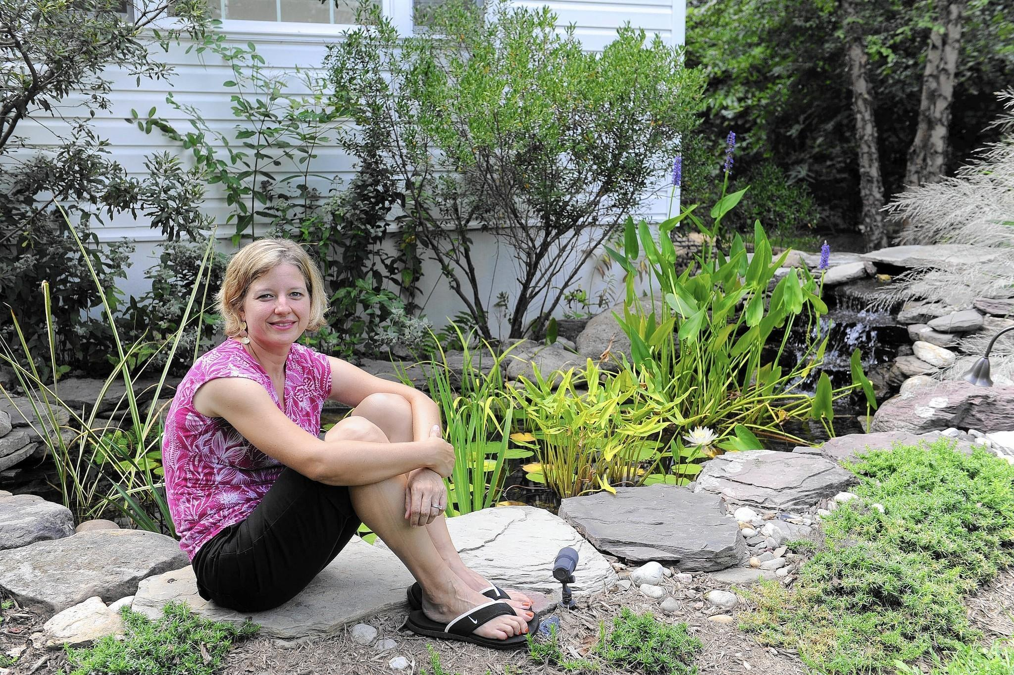 "Janine Pollack has created a ""Bay Wise"" garden around her home. Here, she sits in front of her backyard pond."