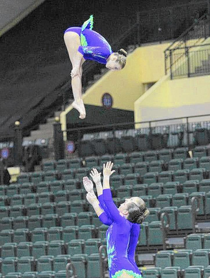 Hannah Silverman (in air) performs with teammates Christina Antoniades and Emily Ruppert in this photo from the 2012 Acro World Age Group Competitions in Lake Buena Vista, Fla. Photo by Brian Kincher, courtesy USA Gymnastics