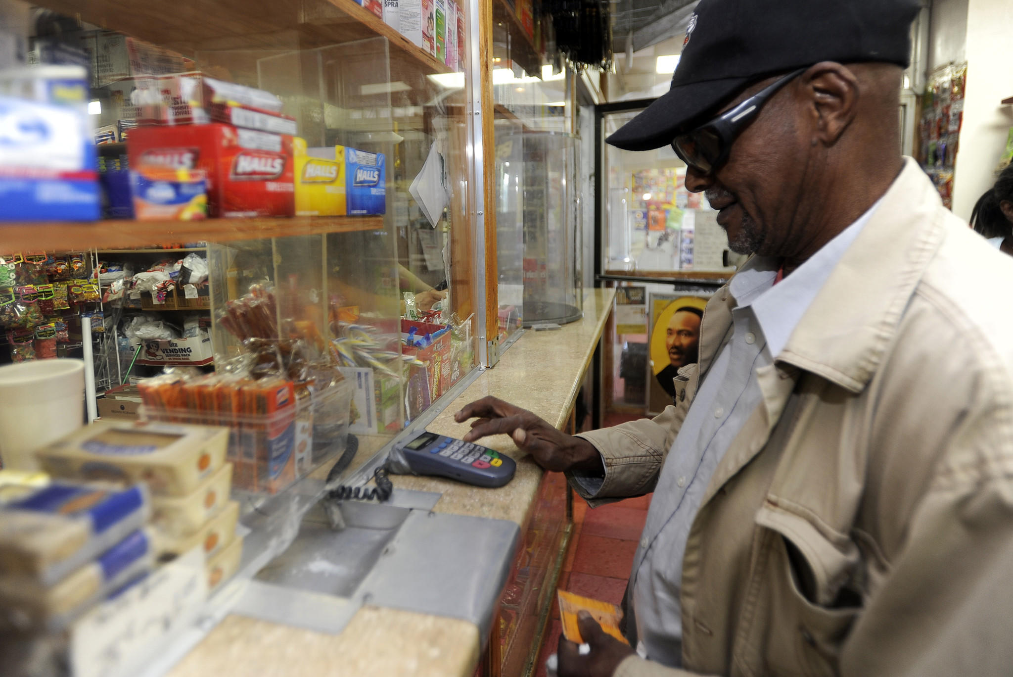 Customer James Gaymon uses a PIN pad to make a purchase with food stamps at the A to Z convenience store on Park Heights Avenue.