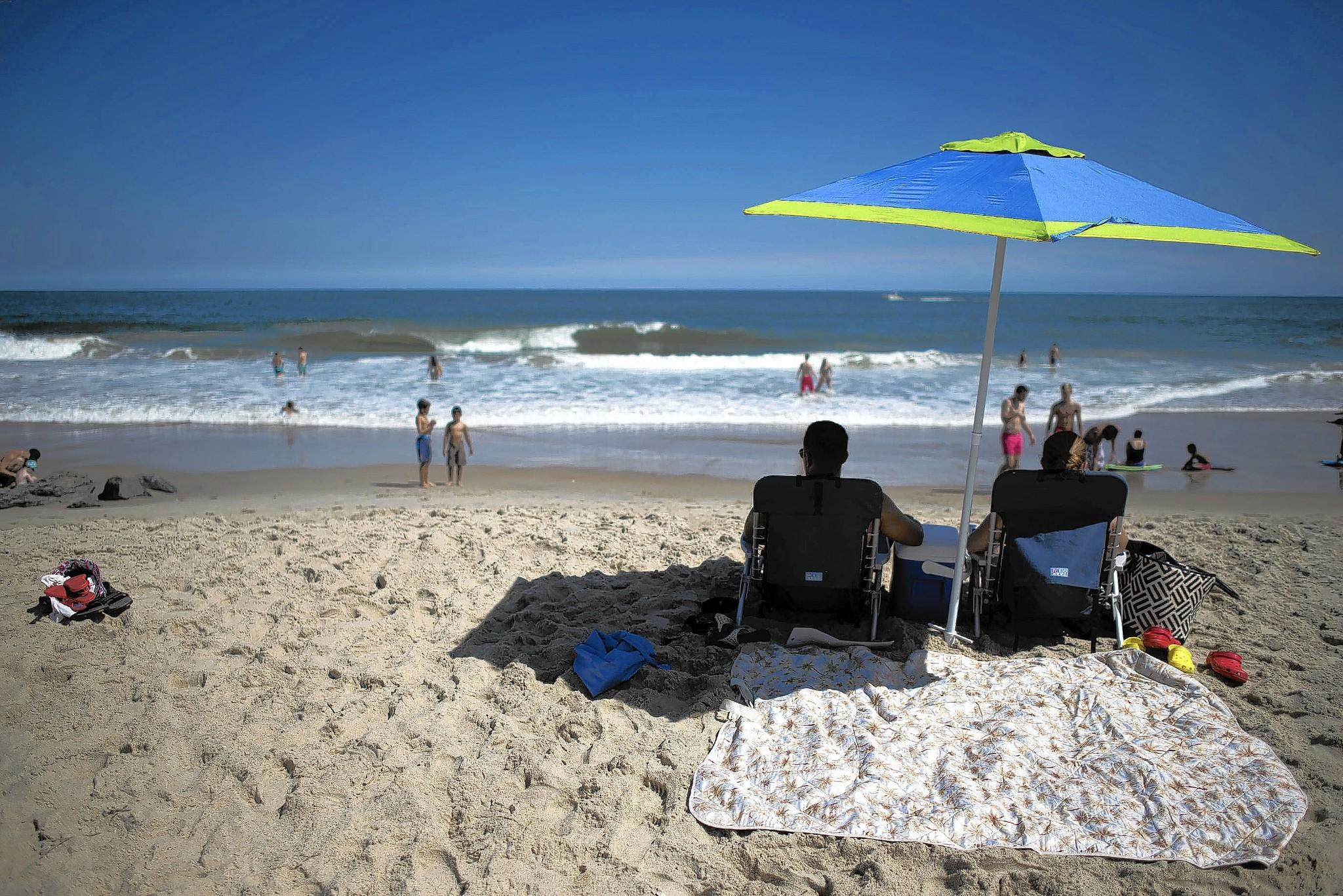 Ocean City beachgoers relaxing on the beach in late August, as the summer season draws to a close.