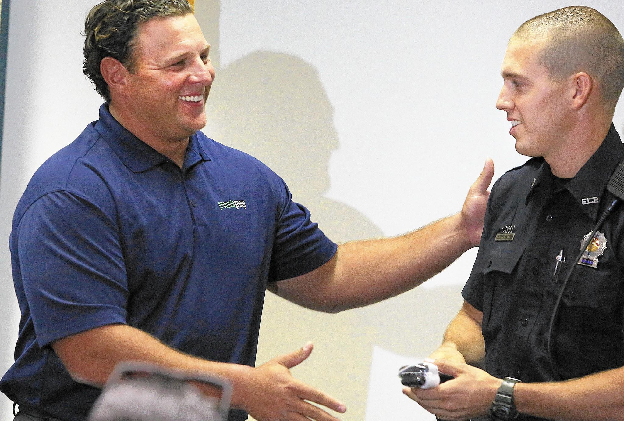Davie Resident, Jeremy Wehby, left, thanks Fort Lauderdale police officer Nick Rollins for saving his wife from potentially bleeding to death after an accident at Vibe nightclub.
