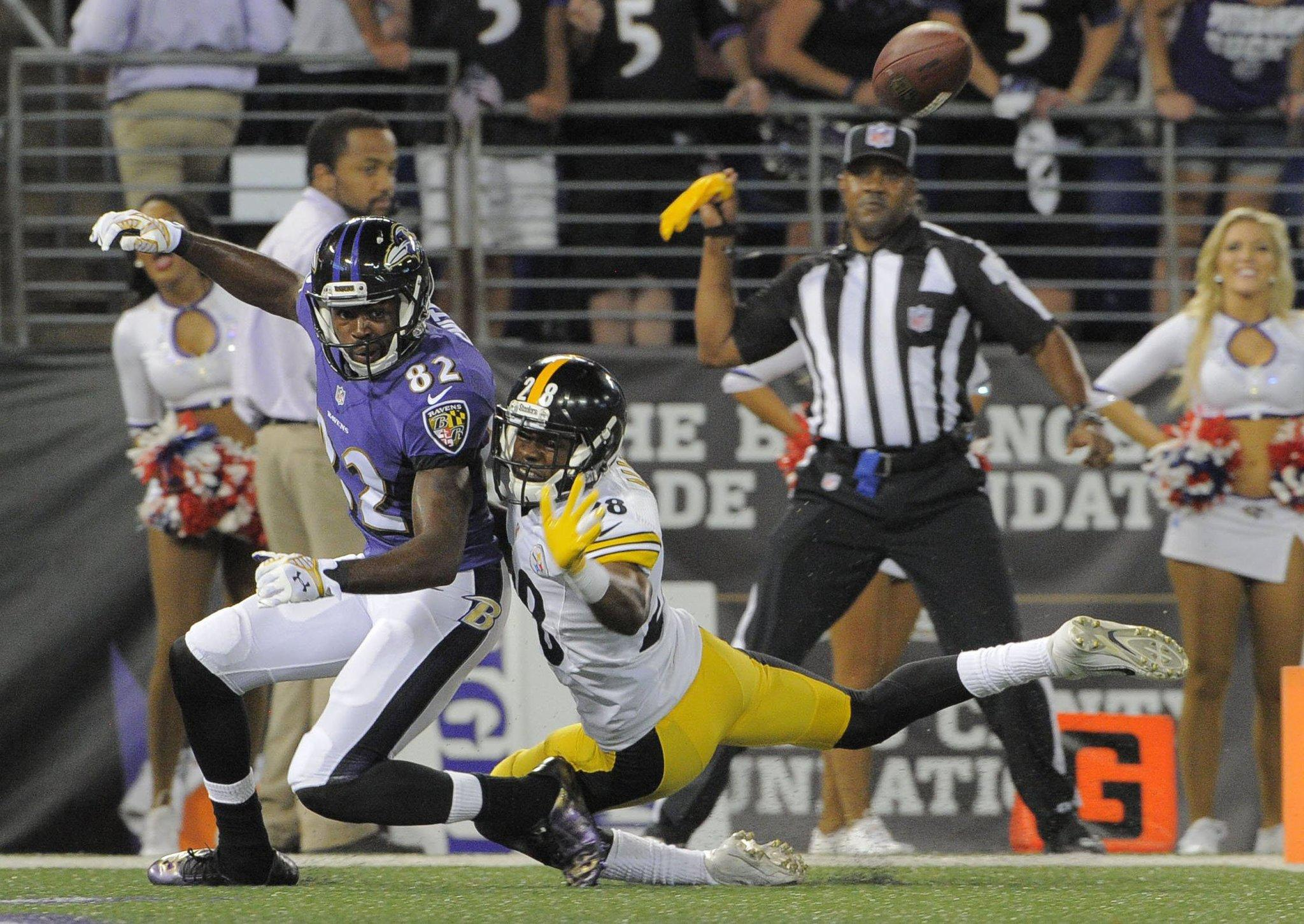 An official prepares to throw a penalty flag for pass interference as the Pittsburgh Steelers' Cortez Allen tangles with the Ravens' Torrey Smith during the first quarter.