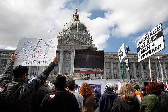 SAN FRANCISCO,CA: People gather to watch a large television screen at City Hall prior to the California Supreme Court hearing on same-sex marriages, in San Francisco, California March 5, 2009. Proposition 8, passed by California voters in November, amends the state constitution to provide that only marriage between a man and a woman is recognized in California.