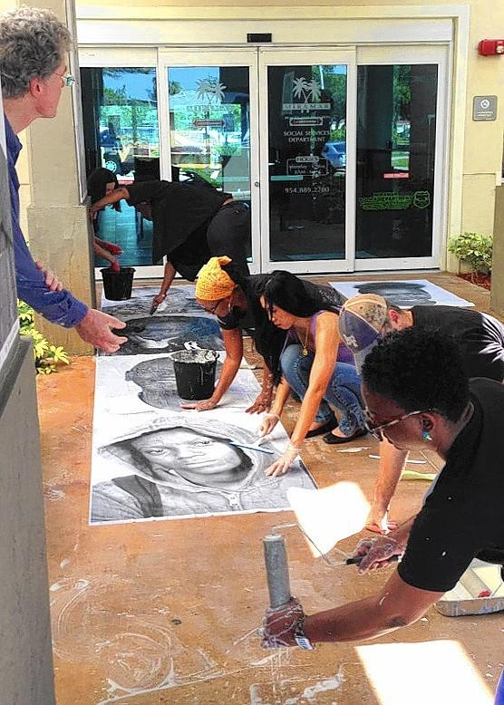 Locals install larger-than-life photographs of Miramar residents at the Miramar Multi-Sports Complex as part of Broward County's 100th birthday celebration. (Submitted photo)