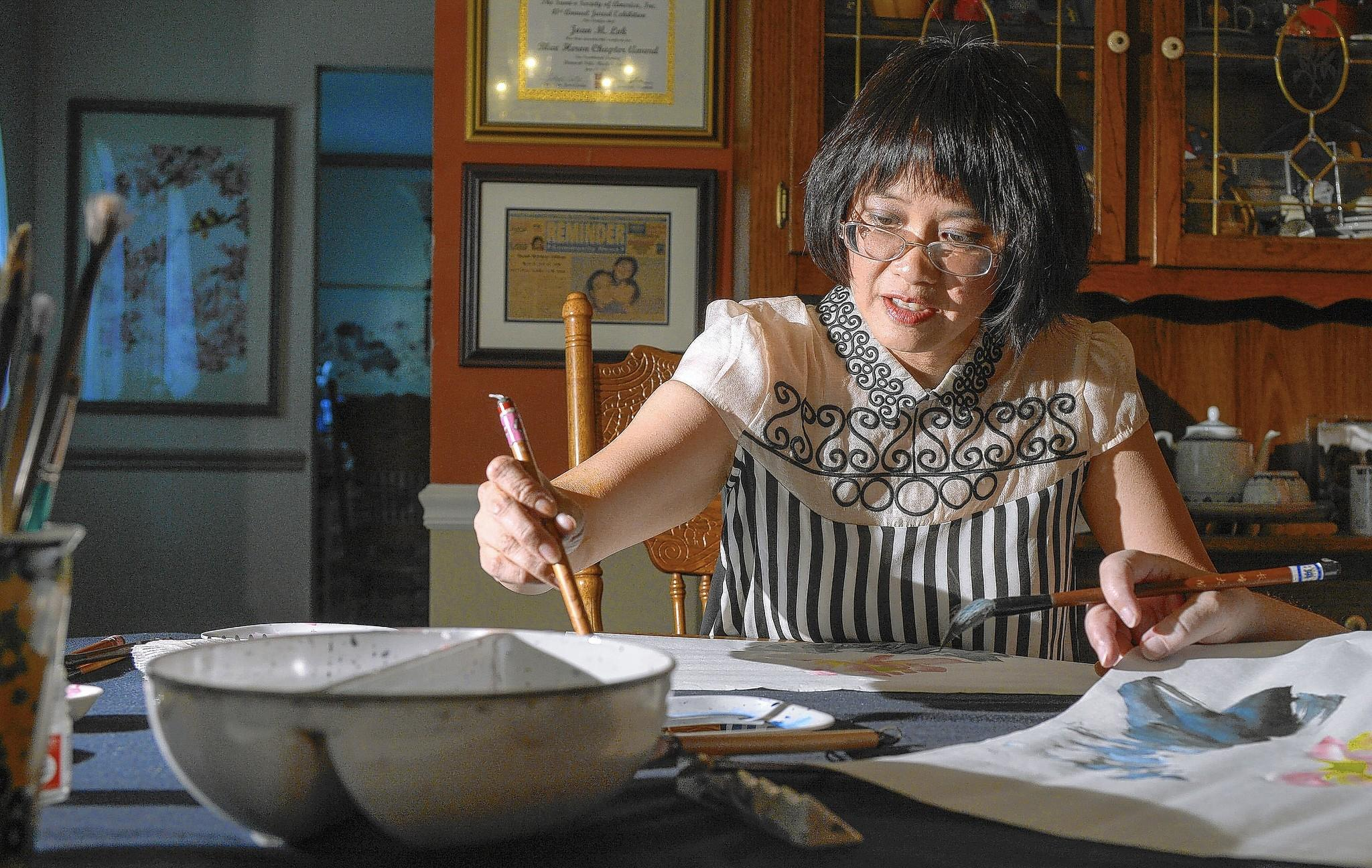 Joan Lok specializes in the art of Chinese brush painting. Barron's Educational Series Books has just published a book of her work and teachings that will come out Oct. 1. On Friday, September 12, she works with a student at her dining room table in Columbia.