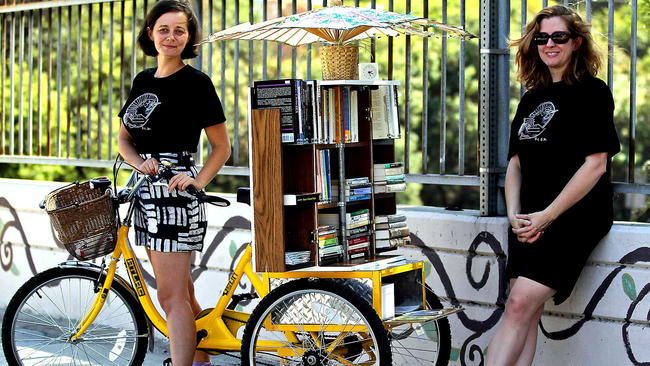 Image of two white women in front of a mobile (tricycle) library.