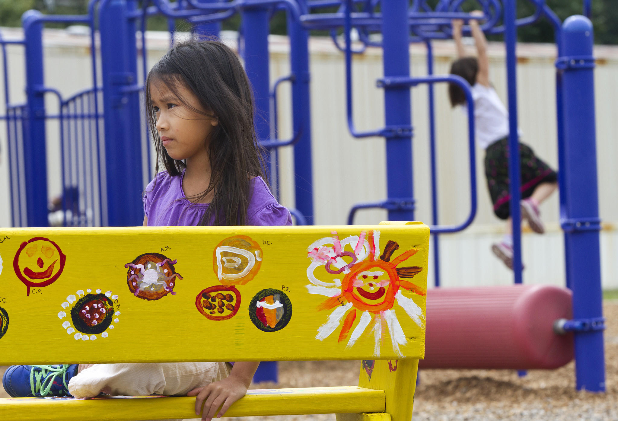 Eva Robinson, a second-grade student at Waller Mill Elementary School, sits on a buddy bench on the playground on Tuesday afternoon. Buddy benches, a new initiative by the York County School Division, offer students a place to sit when they are lonely and would like to find a friend.