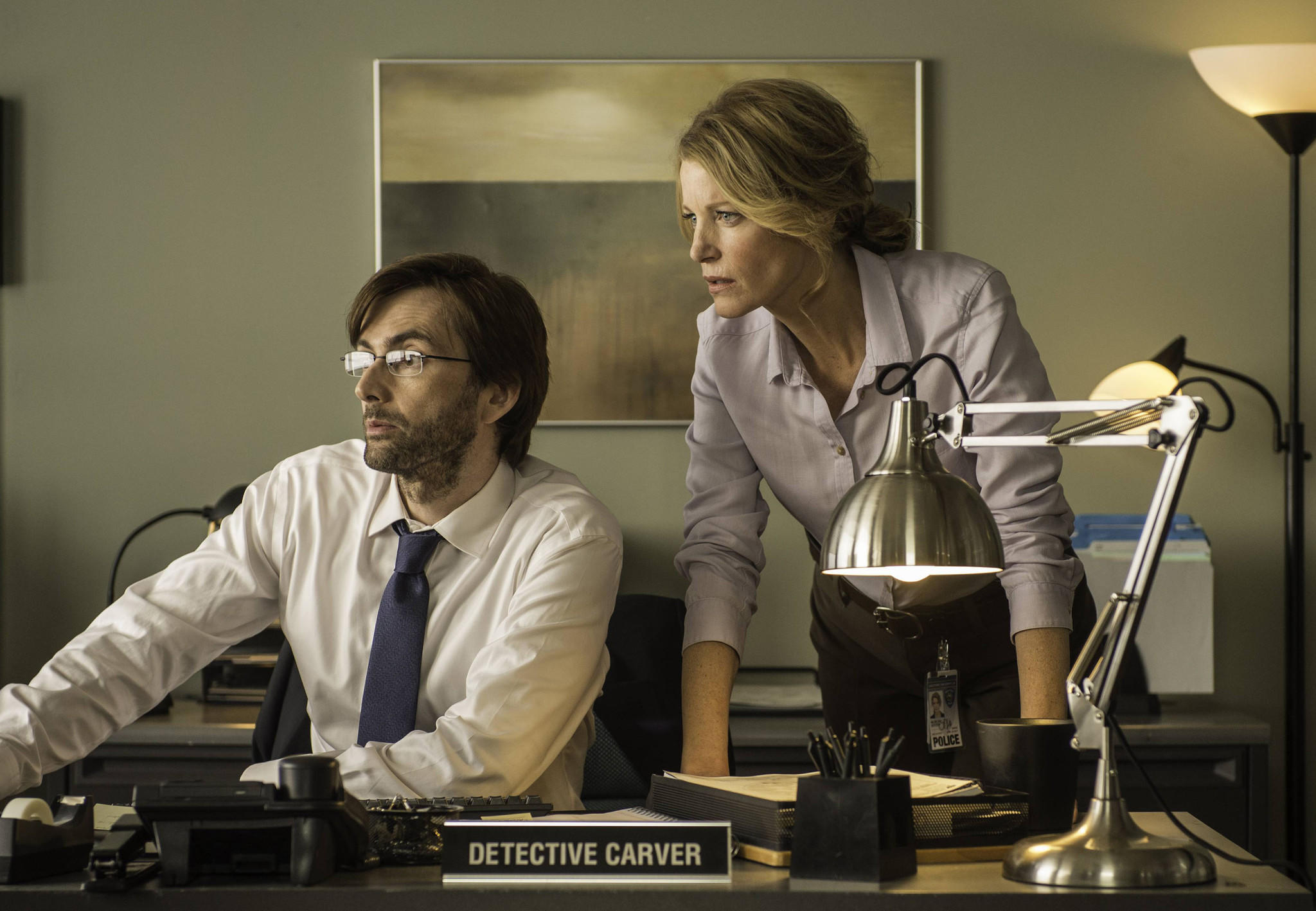 "Detectives Ellie Miller (Anna Gunn) and Emmett Carver (David Tennant) examine a piece of evidence in ""Gracepoint,"" which debuts Thursday at 9 p.m. on Fox."